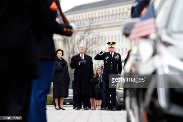 Former President George W Bush and former first lady Laura Bush put their hands over their hearts as a joint services military honor guard carries...