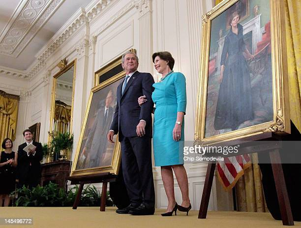 Former President George W Bush and former first lady Laura Bush stand in between their offical portraits during the unveiling ceremony in the East...