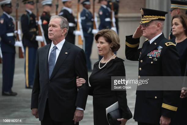 Former President George W Bush and his wife Laura watch as the casket of President George HW Bush is carried from St Martin's Episcopal Church...