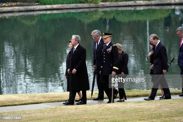 Former President George W Bush and Laura Bush along with Jeb and Columba Bush Neil and Maria Bush and Marvin Bush follow the flagdraped casket of...