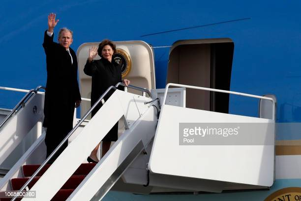 Former President George W Bush and Laura Bush wave as they board Special Air Mission 41 to fly to Houston with the casket of former President George...