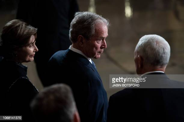Former president George W Bush and wife Laura Bush await the arrival of the flagdraped casket of former president George HW Bush at the US Capitol...