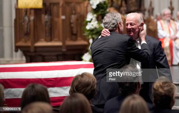 Former President George W Bush embraces former Secretary of State James Baker right after he gave a eulogy during the funeral for former President...