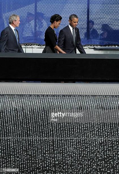 Former President George W Bush First Lady Michelle Obama and and President Barack Obama walk past the North Pool of the 9/11 Memorial during the...