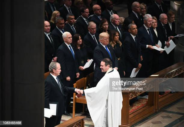 Former president George W Bush fist bumps Rev Dr Russell Levenson Jr of St Martin's Episcopal Church in Houston TX at the conclusion of a funeral...