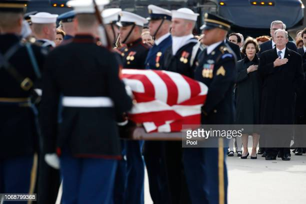 Former President George W Bush former first lady Laura Bush and other family members watch as the flagdraped casket of former President George HW...