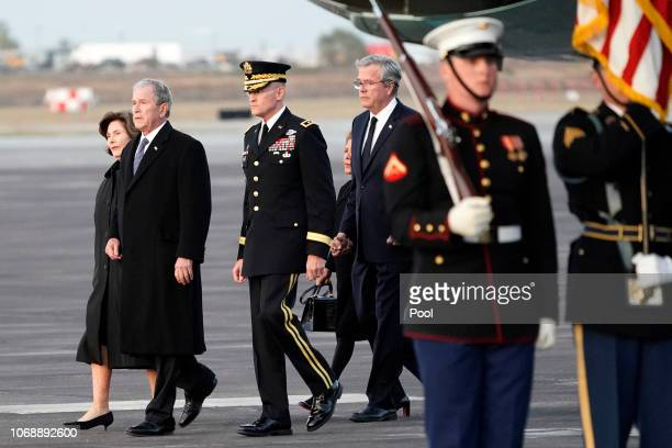 Former President George W Bush former first lady Laura Bush former Governor of Florida Jeb Bush and his wife Columba Bush walk past the flag draped...