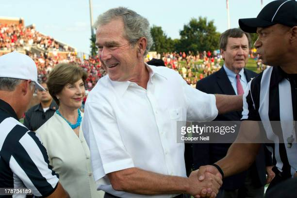 Former President George W Bush gives the coin toss as his wife Laura Bush looks on before kickoff between the Texas Tech Red Raiders and the SMU...