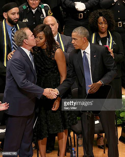 Former President George W Bush kisses First Lady Michelle Obama while shaking hands with President of the United States Barack Obama during the...