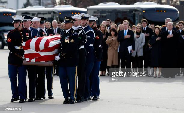 Former President George W Bush Laura Bush and other family members watch as the flagdraped casket of former President George HW Bush is carried by a...