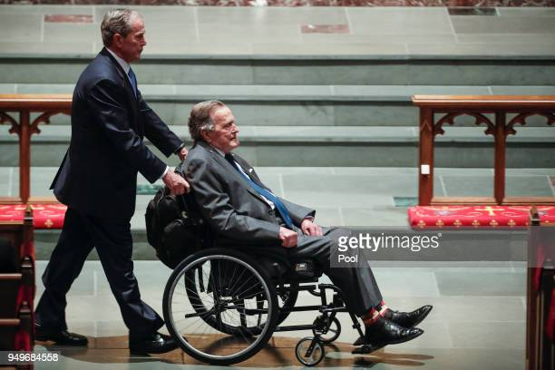 Former president George W Bush left wheels his father former president George HW Bush into the church for the funeral for former first lady Barbara...