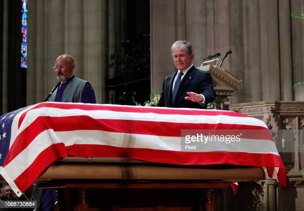 Former President George W Bush puts his hand on the flagdraped casket of former President George HW Bush after giving a eulogy during the State...