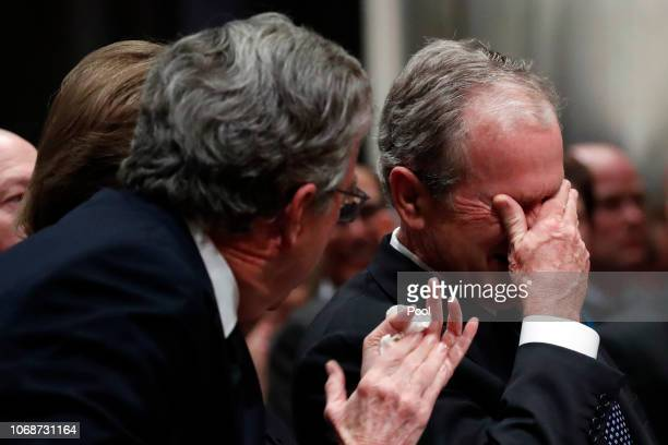 Former President George W Bush right cries after speaking during the state funeral for his father former President George HW Bush at the Washington...