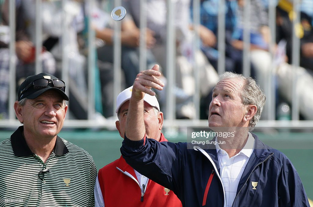 Former President George W. Bush tosses a coin in front of the International Team captain Nick Price and of the United States Team captain Jay Hass at the start of the Thursday foursomes matches at The Presidents Cup at Jack Nicklaus Golf Club Korea on October 8, 2015 in Songdo IBD, Incheon City, South Korea