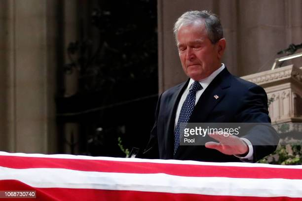 Former President George W Bush touches the casket of his father former President George HW Bush at the State Funeral at the National Cathedral...