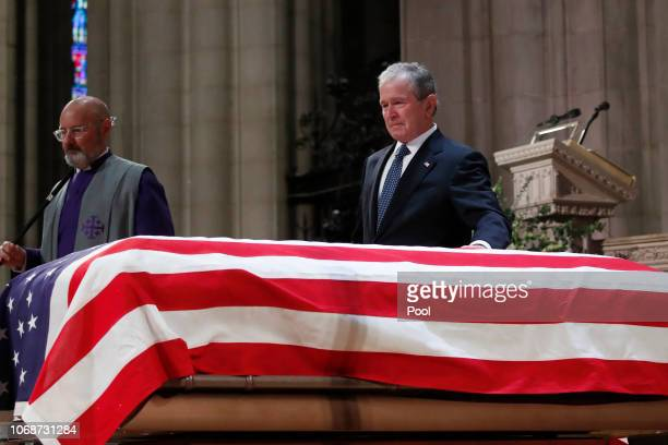 Former President George W Bush touches the casket of his father former President George HW Bush at the State Funeral at the Washington National...