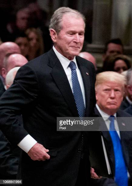 Former President George W Bush walks past President Donald Trump to speak during the State Funeral for his father former President George HW Bush at...