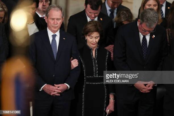 TOPSHOT Former president George W Bush wife Laura Bush and brother Jeb Bush stand before the flagdraped casket of former president George HW Bush at...
