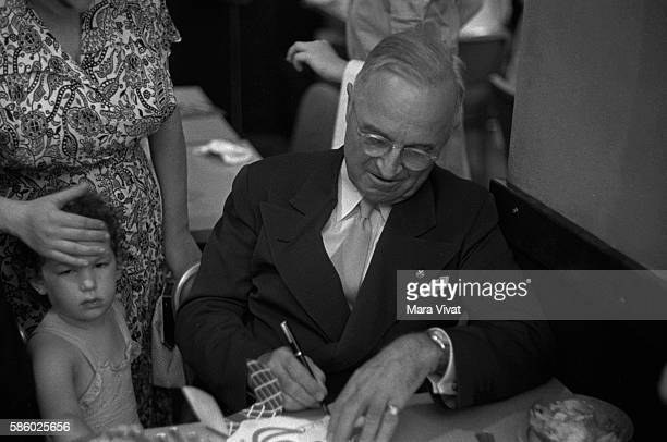 Former president Harry Truman signs a card for a young child in a restaurant After his presidency ended in 1953 Truman retired to his hometown of...