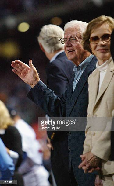 Former President Jimmy Carter does the tomahawk chop as wife Rosalyn Carter watches prior to Game 5 of the National League Division Series between...