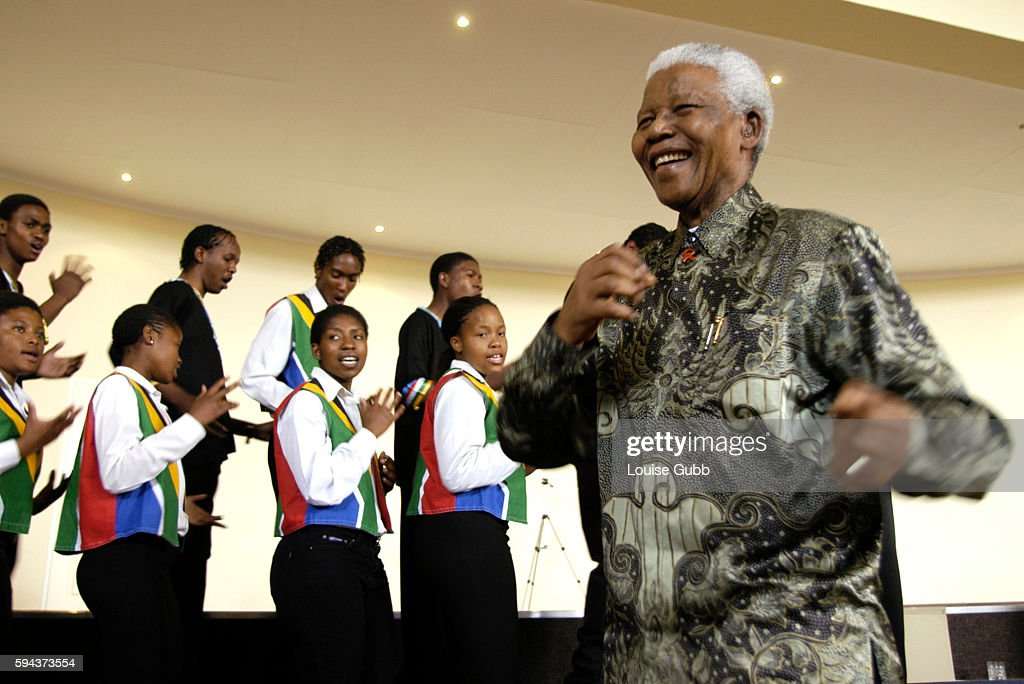 Former President Nelson Mandela, 85, dances joyfully to the rhythms of the Sparrow school choir during his traditional pre-Christmas visit to needy institutions supported financially by the Nelson Mandela Children's Fund. Addressing the students, he emphasized the importance of a good education and the need to fight the stigmatization of people with HIV/Aids.