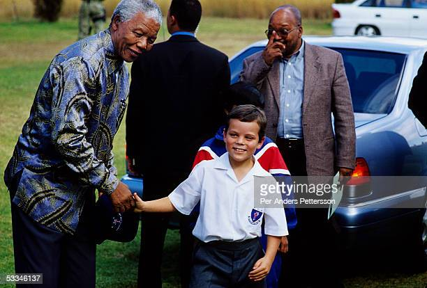 Former President Nelson Mandela of South Africa smiles as he greets a white school boy during an election stop on May 1 1999 in Eastcourt South...