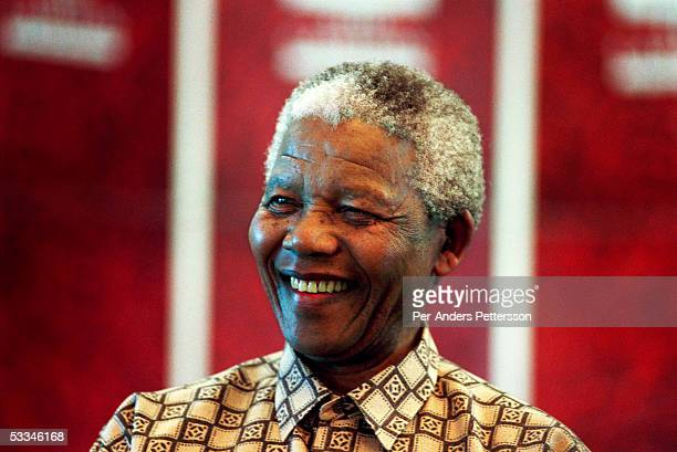 Former President Nelson Mandela of South Africa smiles as he talks to visitors on March 8, 1999 in his residence in Houghton, a suburb of...