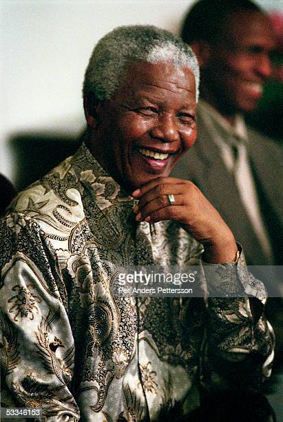 Former President Nelson Mandela of South Africa speaks to visitors on March 8, 1999 in his residence in Houghton, a suburb of Johannesburg, South...
