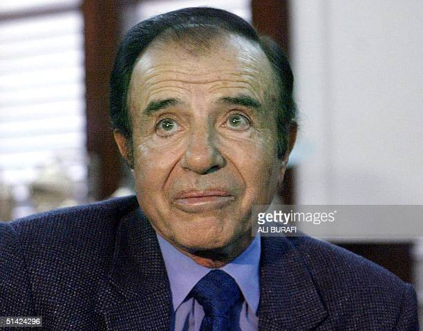 Former president of Argentina Carlos Menem talks with supporters in the governor's residence in the province of Rioja 25 July 2002 New accusations...