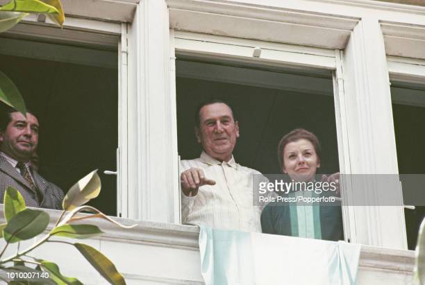 Former President of Argentina Juan Peron pictured with his wife Isabel Martinez de Peron as he waves to supporters from a balcony at a house in...
