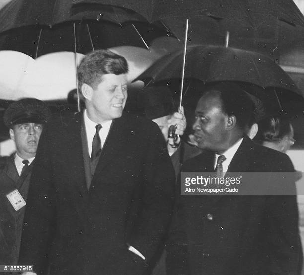 Former president of Ghana Kwame Nkrumah and former United States President John F Kennedy walking at an airport during a rainstorm February 1961