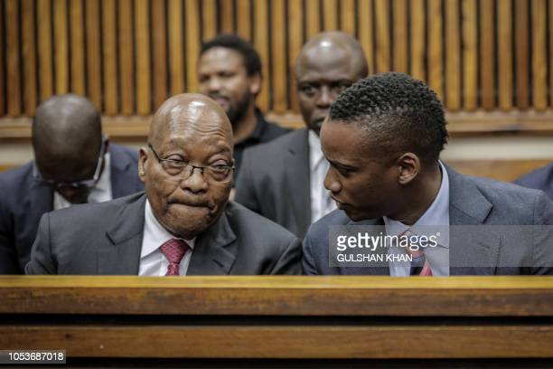 Former President of South Africa, Jacob Zuma speaks to his son Duduzane Zuma at the Randburg Magistrates Court on October 26 in Johannesburg. -...