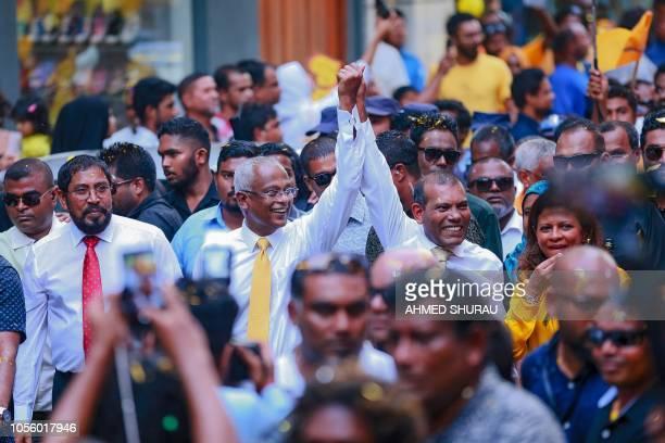 Former president of the Maldives Mohamed Nasheed walks along presidentelect Ibrahim Mohamed Solih while raising their hands after Nasheed returned...