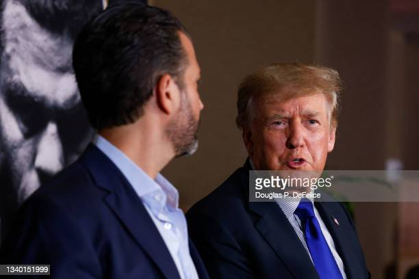 Former President of the United States Donald Trump speaks with Donald Trump Jr. Prior to the fight between Evander Holyfield and Vitor Belfort during...