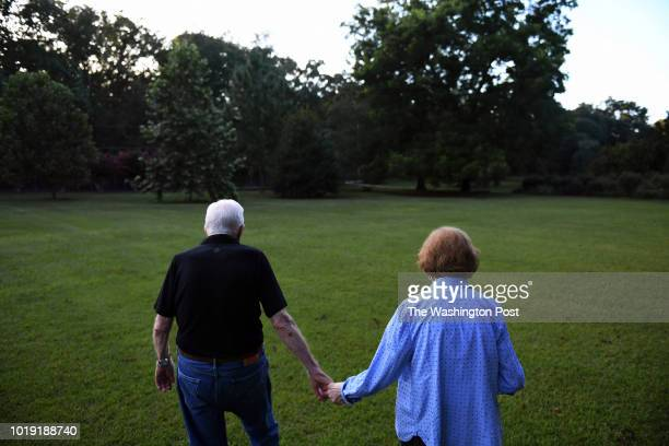 Former President of the United States Jimmy Carter walks with his wife former First Lady Rosalynn Carter towards their home following dinner at a...