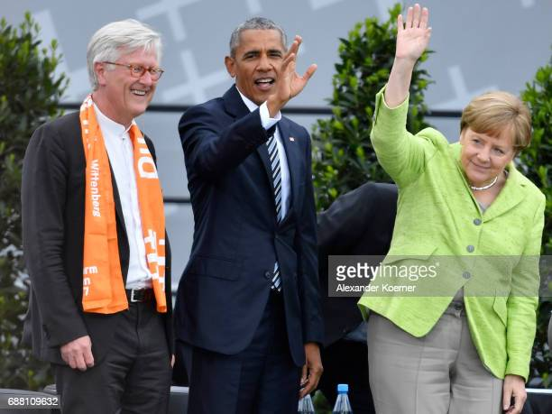 Former President of the United States of America Barack Obama and German Chancellor Angela Merkel walk on stage at the Brandenburg Gate during the...