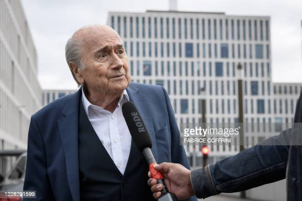 Former president of World football's governing body FIFA, Sepp Blatter speaks to a journalist as he arrives at the building of the Office of the...