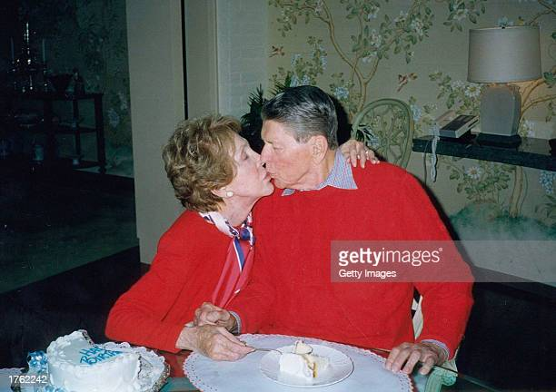 Former President Ronald Reagan gets a kiss from his wife Nancy on the occasion of his 89th birthday February 6 2000 at their home in Bel Air...