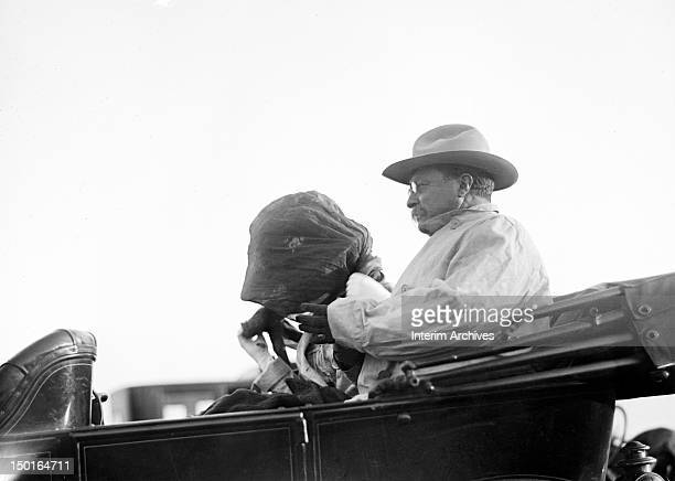 Former president Theodore Roosevelt sits in an automobile and watches a polo match early twentieth century