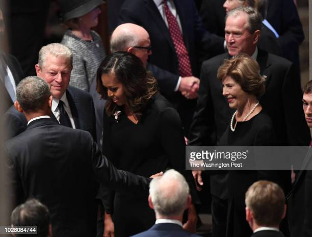 Former Presidents Barach Obama and George Bush with their wives Michelle and Barbara talks with former VP Al Gore at the funeral service at the...