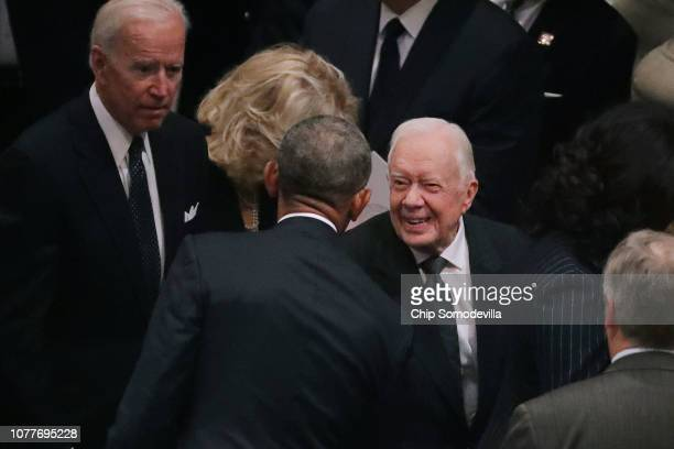 Former presidents Barack Obama and Jimmy Carter greet one another during the state funeral for former President George HW Bush at the National...