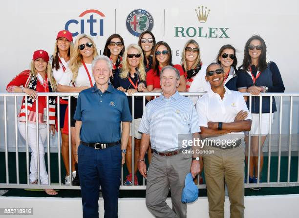 Former Presidents Barack Obama George W Bush and Bill Clinton pose with the US Team wives and girlfriends during the first round of the Presidents...