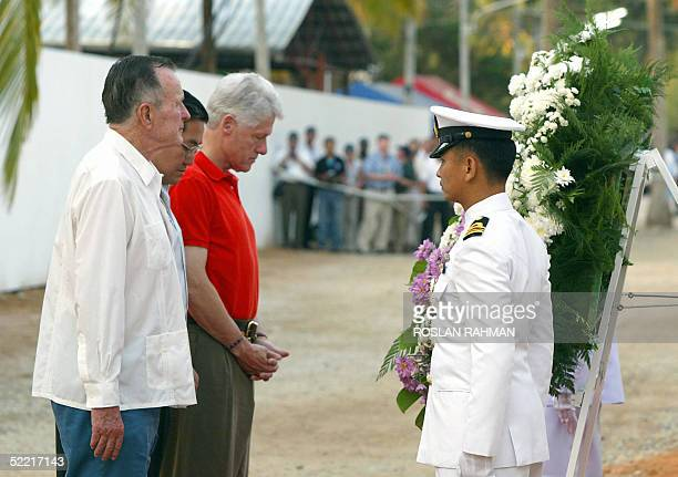 US former presidents George Bush Senior and Bill Clinton with the Thailand foreign minister Surakiat Sathirathai par a respect during a laying of...