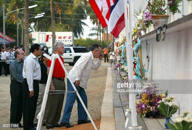 US former presidents George Bush Senior and Bill Clinton with the Thailand foreign minister Surakiat Sathirathai take a closer look of the...