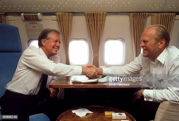 Former presidents Jimmy Carter and Gerald Ford shake hands on Air Force One while en route to Cairo for the funeral of Egyptian President Anwar Sadat...