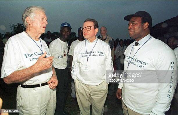Former presidents Jimmy Carter of the United States and Nicephore Soglo of Benin and former US Senator Paul Simon visit a polling station as voting...