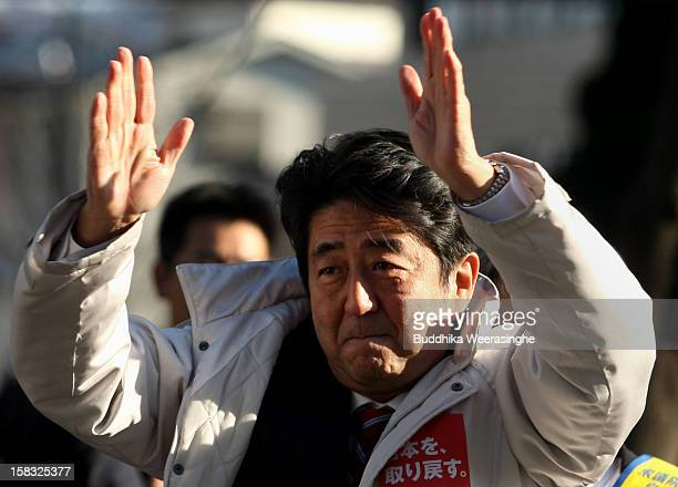 Former Prime Minister and leader of Japan's main opposition Liberal Democratic Party Shinzo Abe gives a speech from the roof of a campaign car during...