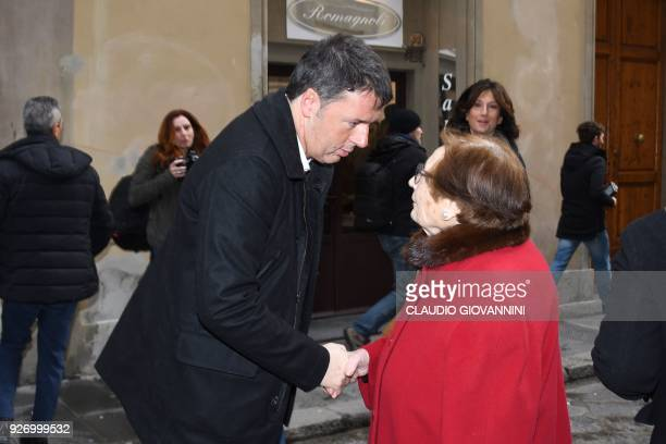 Former Prime Minister and leader of the Democratic Party Matteo Renzi shakes hands to a woman outside a polling station on March 4 2018 in Florence...