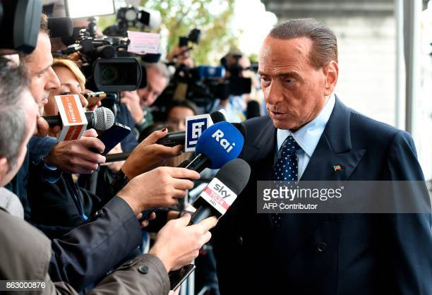 Former Prime Minister and president of Italian right-wing party Forza Italia Silvio Berlusconi speaks to journalists as he arrives at a meeting of...