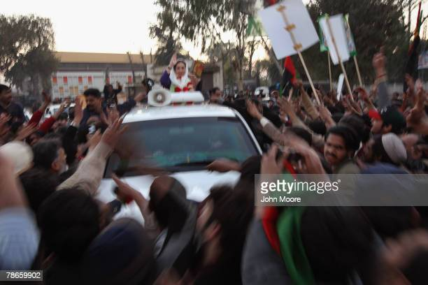 Former Prime Minister Benazir Bhutto waves from her car just seconds before being attacked on December 27, 2007 in Rawalpindi, Pakistan. The...